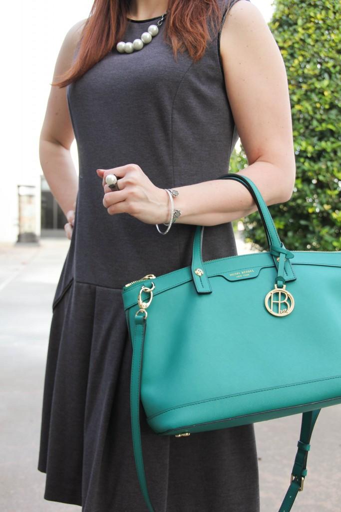 gray sheath dress pearl jewelry and green purse