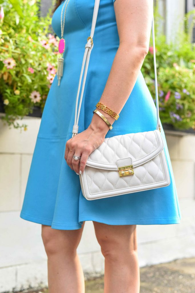 blue fit and flare dress with white quilted crossbody bag