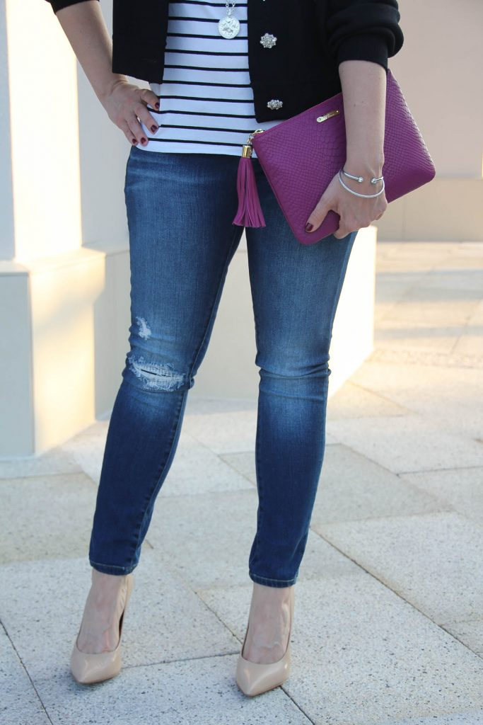 LadyinViolet style her favorite distressed jeans under 100 with a casual striped tee and dark pink clutch.