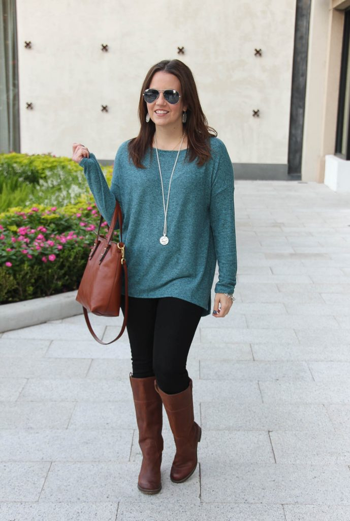 Fashion Blogger LadyinViolet wears a fall outfit idea with a teal sweater and brown riding boots.