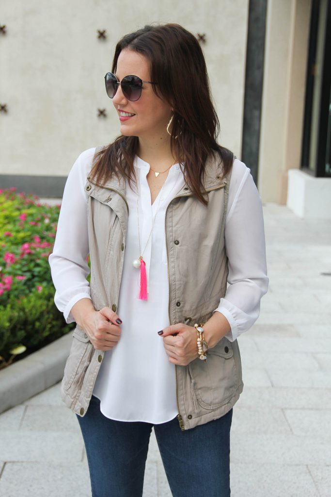 Khaki utility vest with white blouse and pink tassel necklace.