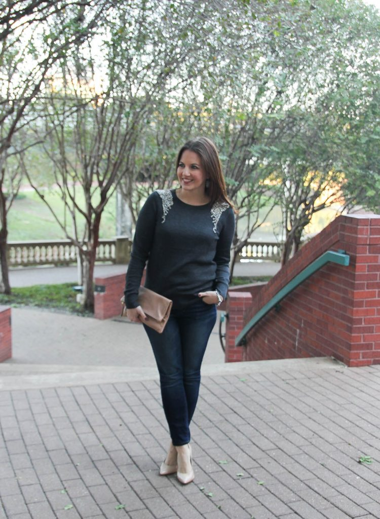 Houston Fashion Blogger wears a holiday outfit idea with an embellished sweater, dark skinny jeans, and heels.
