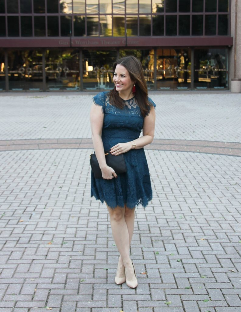 Houston Fashion blogger wears a holiday party outfit featuring a teal lace dress and red tassel earrings.