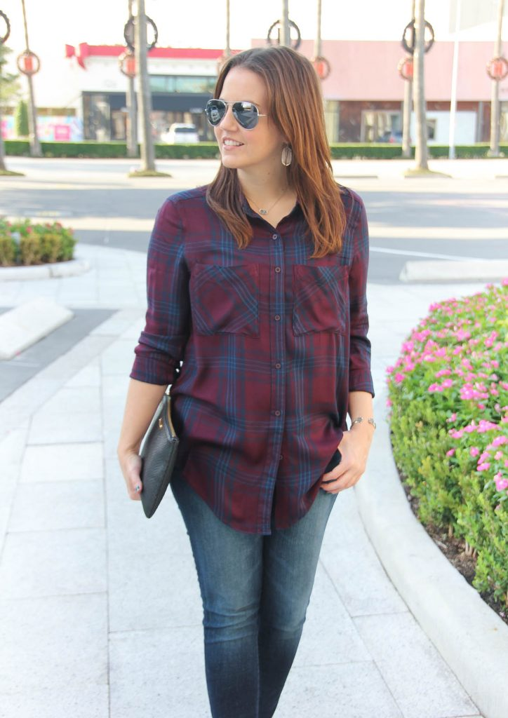 Houston Fashion Blogger wears a fall outfit featuring a burgundy and navy plaid tunic.