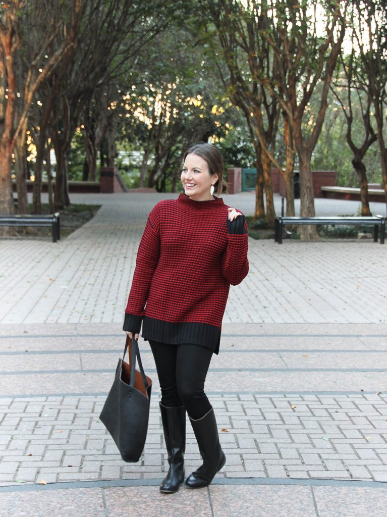 Houston Fashion Blogger styles a winter outfit idea featuring a red long sweater with black skinny jeans and riding boots.
