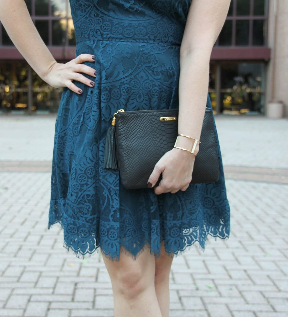 Houston Fashion Blogger Lady in Violet styles a holiday office party outfit including a teal lace dress, gold bracelet and black clutch.