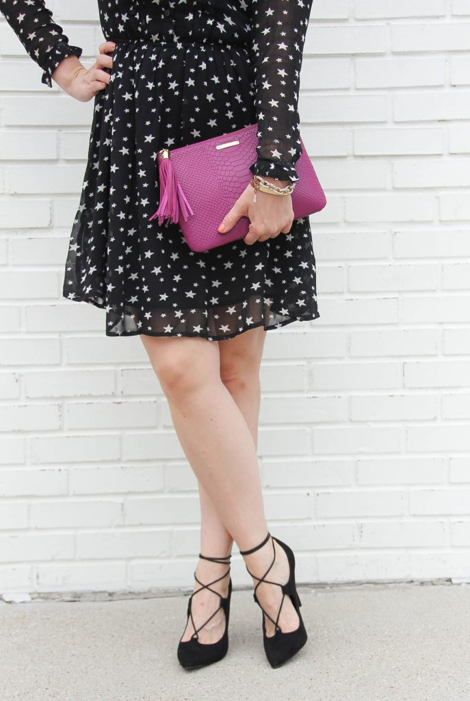 Houston Fashion Blogger, Karen Rock wears black lace up heels, a star print dress and carries a magenta clutch for a holiday party outfit.