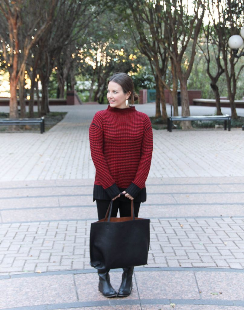 Houston Fashion Blogger, Lady in Violet wears a red Christmas sweater outfit with jeans, boots and a tote bag.