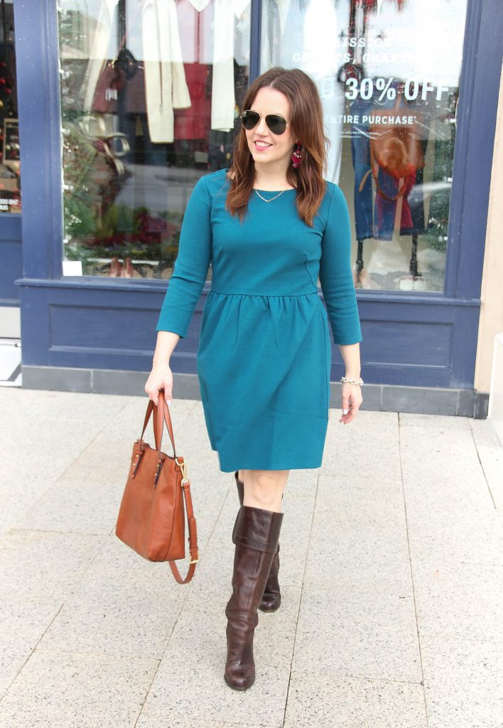 Houston fashion blogger wears a teal fit and flare dress with tall brown boots for the office.