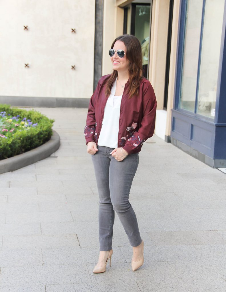 Houston Fashion Blogger styles a winter outfit idea featuring a floral bomber jacket, gray skinny jeans and heels.
