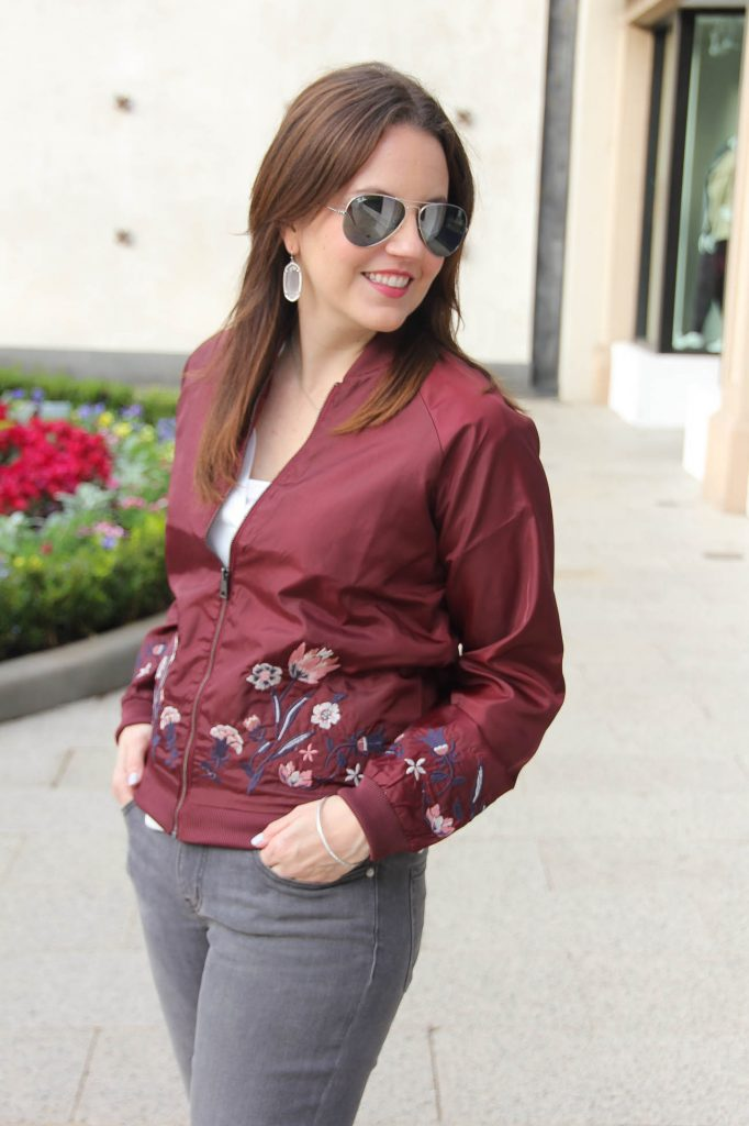 Houston fashion blogger, Lady in Violet wears a burgundy floral bomber jacket with rayban aviators in silver mirror.