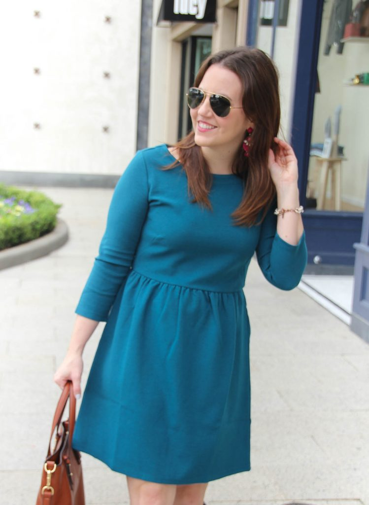Houston Fashion Blogger wears a Loft teal fit and flare dress for work with boots and pink earrings.