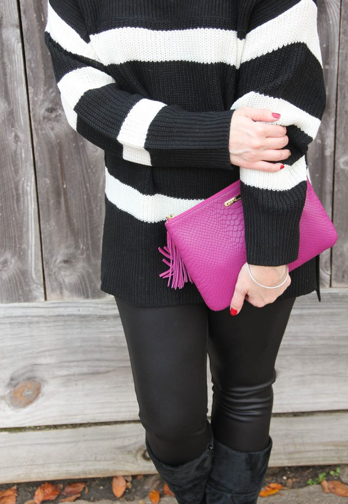 Lady in Violet, Houston fashion blogger styles a winter party outfit featuring leather leggings, a pink clutch, and a striped sweater.