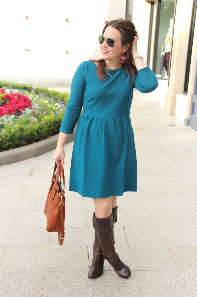 Lady in Violet, Houston fashion Blogger styles a fall work outfit idea featuring a teal dress from loft, brown riding boots and pink earrings.