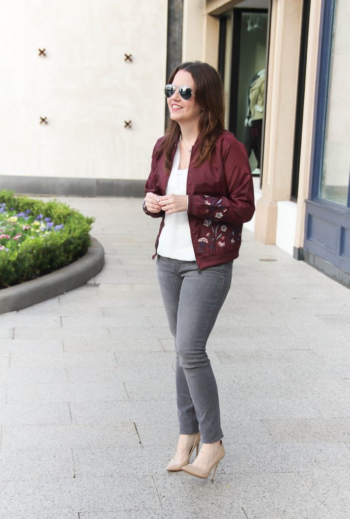 Houston Fashion Blogger Lady in Violet styles a casual weekend outfit featuring a floral bomber jacket and gray jeans with nude heels.