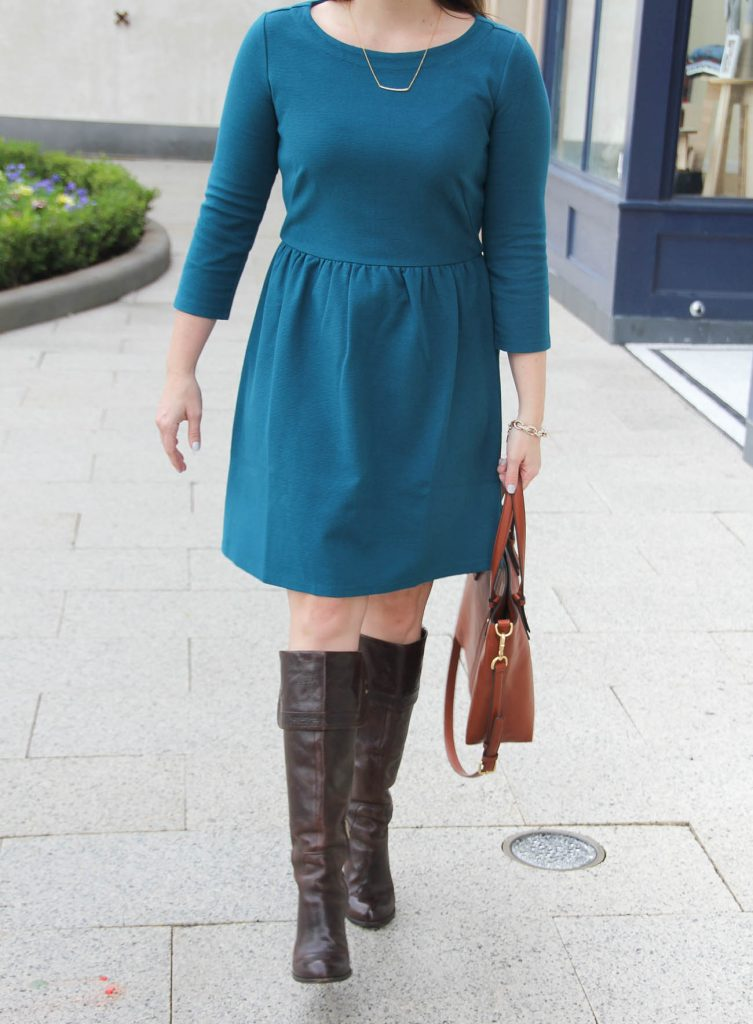 Houston Fashion Blogger wears the teal loft dress with brown tall boots for a work outfit idea.