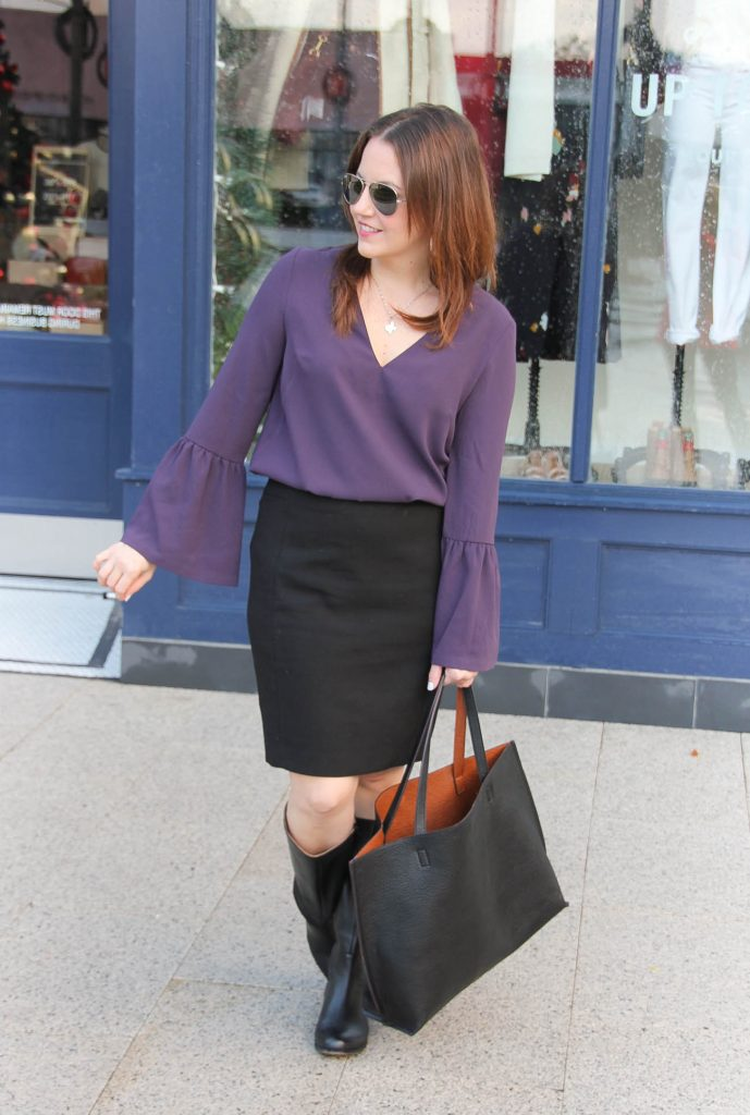 Houston Fashion blogger Lady in Violet styles a winter work outfit featuring a purple bell sleeve blouse with a skirt and boots.