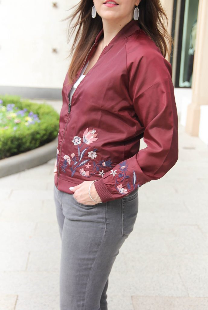 Houston Style Blogger Karen Rock of Lady in Violet wears an embroidered floral bomber jacket from nordstrom with gray skinny jeans and kendra scott elle earrings.