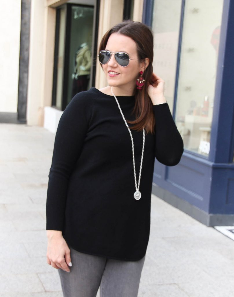 Houston Fashion Blogger Lady in Violet wears a long black wool cashmere sweater with a long silver pendant necklace and dark pink statement earrings.