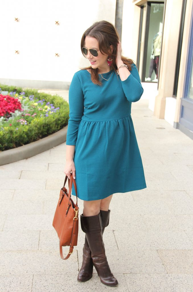 Houston Texas Style Blogger styles a work outfit idea including a teal flare dress with brown riding boots.