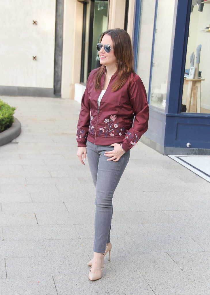 Houston Style Blogger Lady in Violet wears a weekend outfit including a floral bomber jacket with gray jeans and heels.