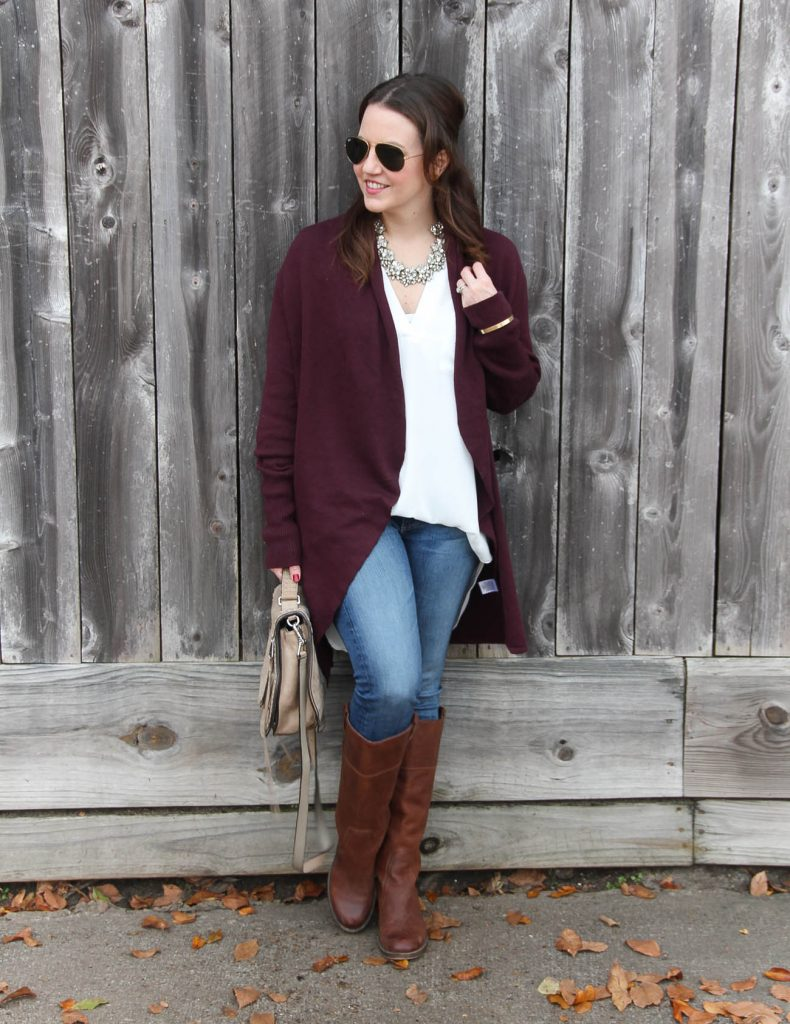 Houston Fashion Blogger Lady in Violet styles a warm winter outfit with a burgundy long cardigan, a white tunic blouse, blue jeans, and brown boots.