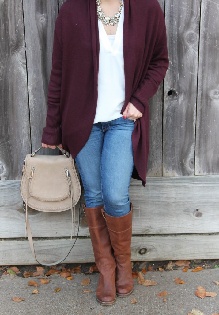 Karen Rock of Lady in Violet styles a casual fall outfit featuring a long cardigan, riding boots, and a saddle bag purse.