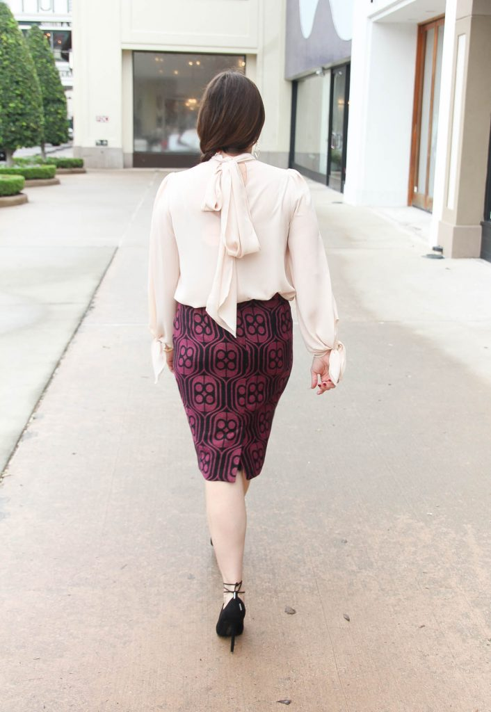 Houston Blogger Lady in Violet styles a work wear outfit including a back tie blouse and pink pencil skirt. Click through for outfit info.