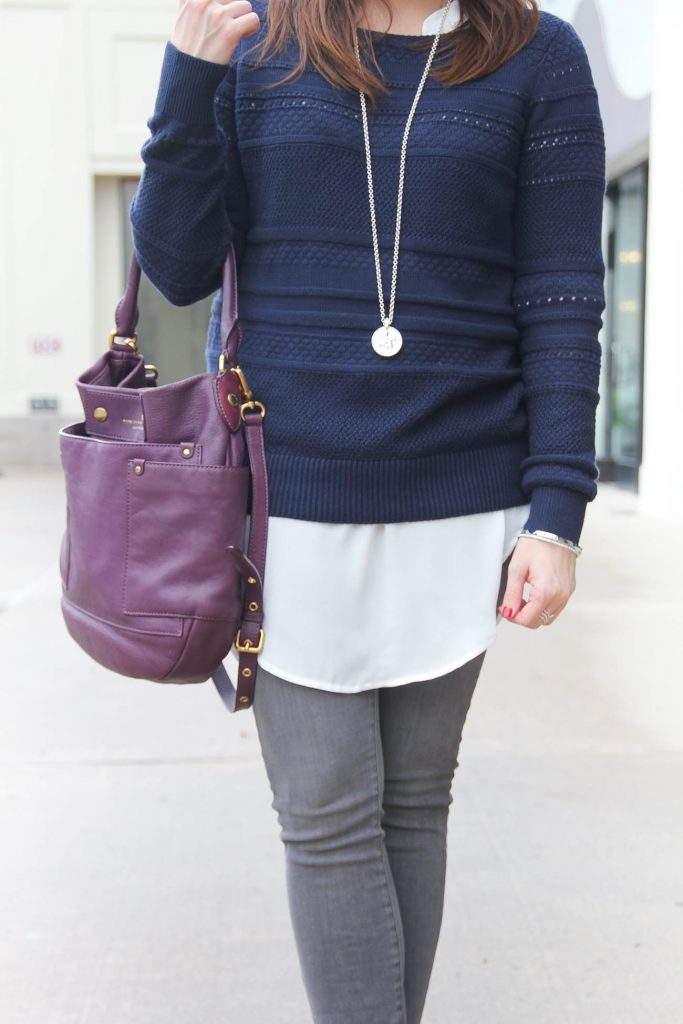 Houston Fashion Blogger wears a winter layered outfit idea featuring a navy sweater over a white tunic and gray jeans. Click through for outfit details.