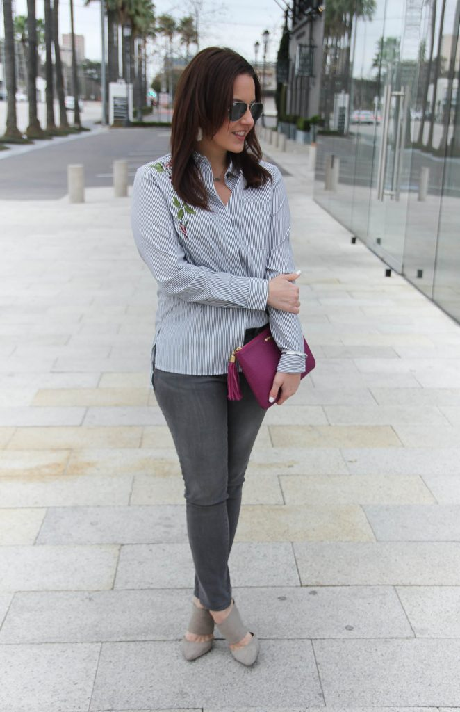 Houston Fashion Blogger wears a date night outfit including a gray striped blouse and gray jeans with suede mules.