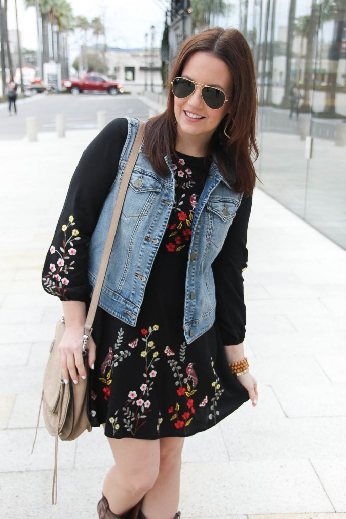 Lady in Violet, a Houston based fashion blogger styles a rodeo outfit idea featuring a denim vest and embroidered dress.