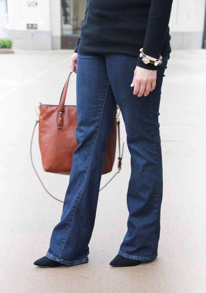 Lady in Violet, a Houston style blogger wears a casual Friday office outfit with flared jeans and a black sweater.