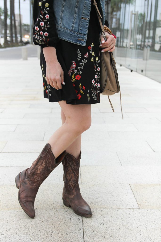 Lady in Violet a Houston blogger styles a houston rodeo outfit idea including cowboy boots, a fit and flare dress, and crossbody saddle bag.