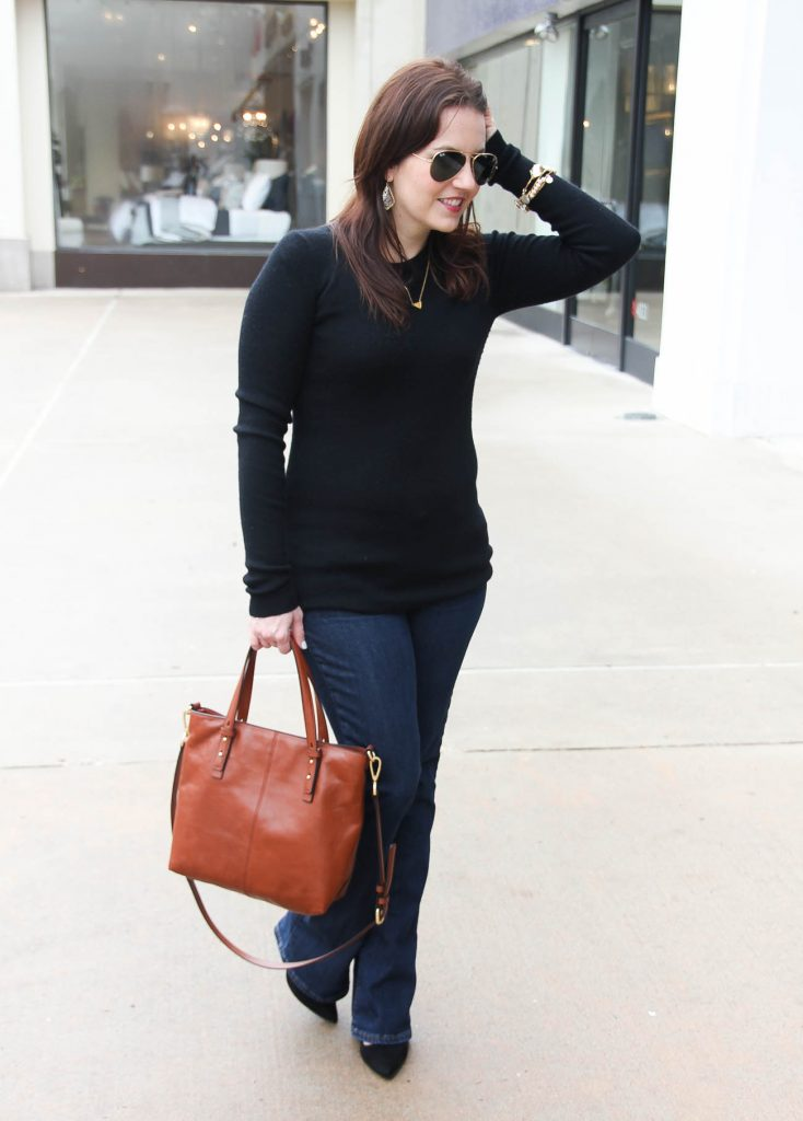 Karen Rock, a Houston based fashion blogger wears a casual winter outfit including a black fitted sweater and bootcut jeans with heels.