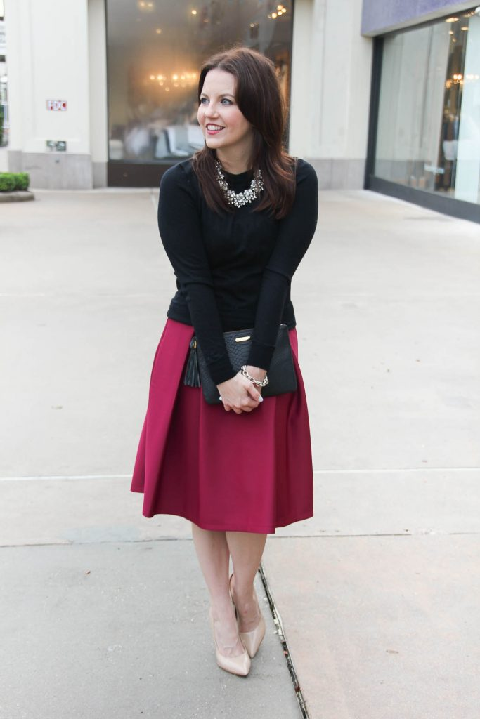 Lady in Violet, a Houston Fashion Blogger wears a winter office outfit including a pink midi skirt and black crewneck sweater.