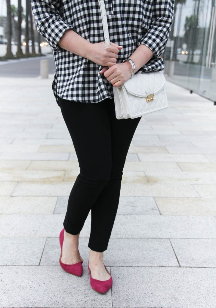 Lady in Violet wears DL1961 black skinny jeans with pink flats and a white crossbody bag.