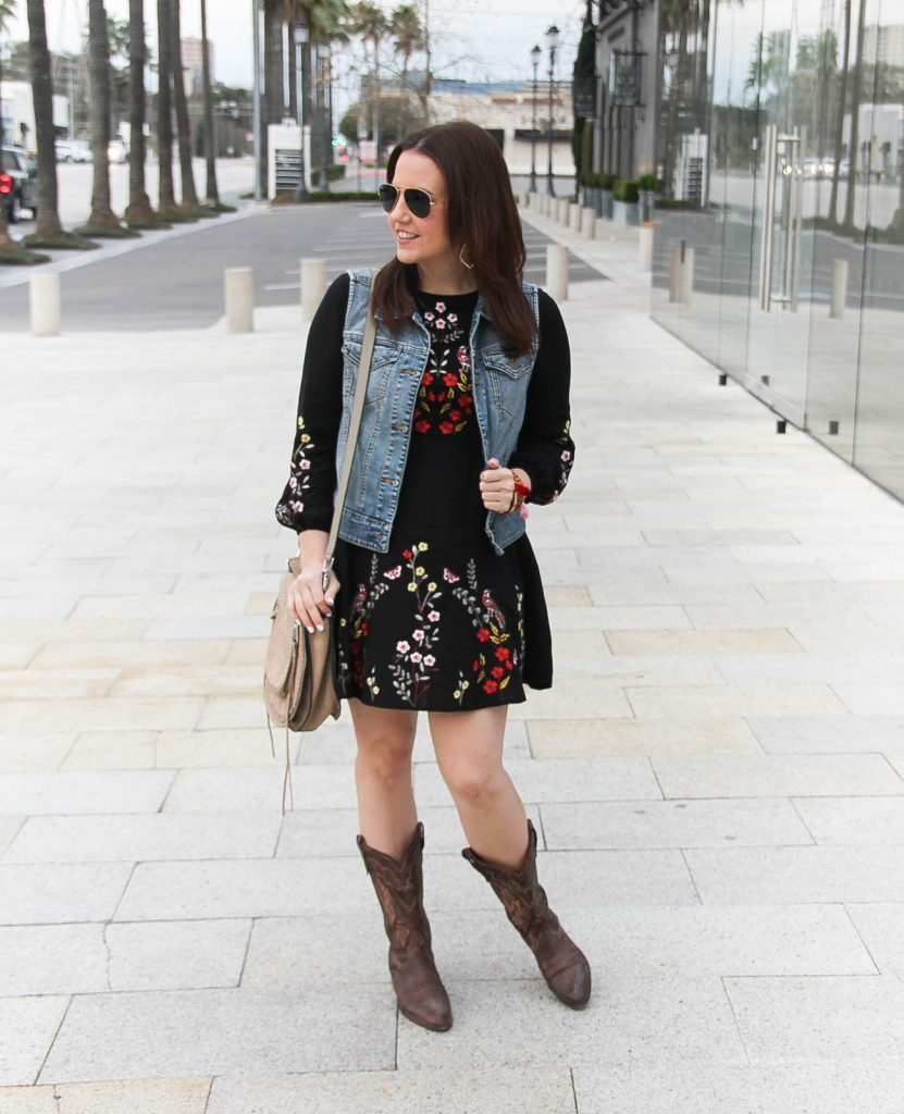 Lady in Violet, houston fashion blogger styles a rodeo outfit idea including an embroidered dress, denim vest, and cowboy boots.