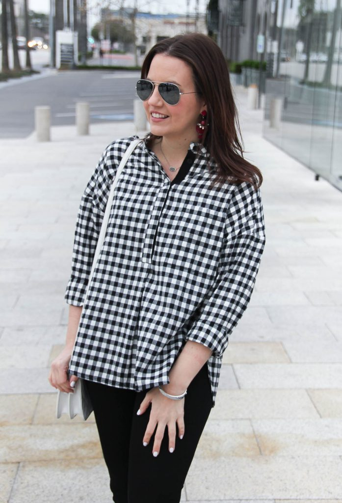 Houston style blogger styles a spring outfit including a gingham plaid top with jeans and pink earrings.