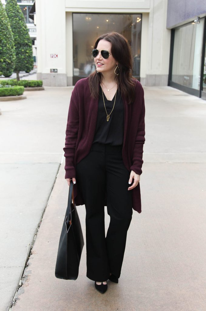 Lady in Violet, a Houston Fashion Blog styles a work outfit idea for cold days featuring a long cardigan and black flared pants.