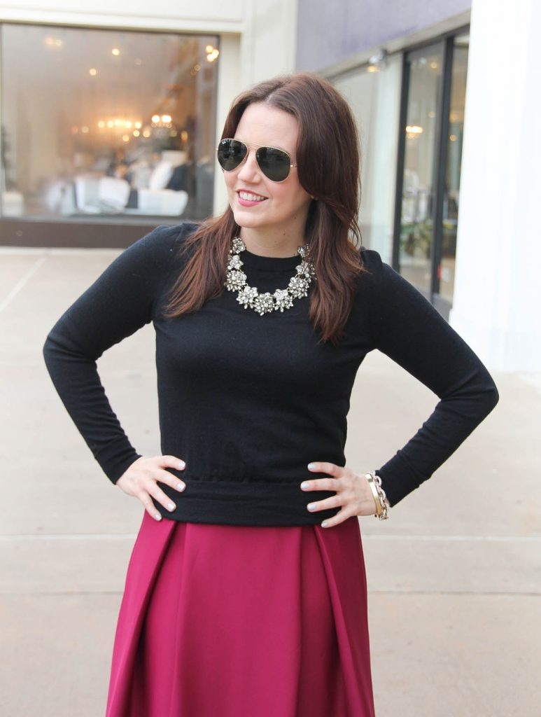 Lady in Violet, a Houston fashion blogger styles a Valentine's Date night outfit idea including a black sweater and statement necklace with a pink skirt.