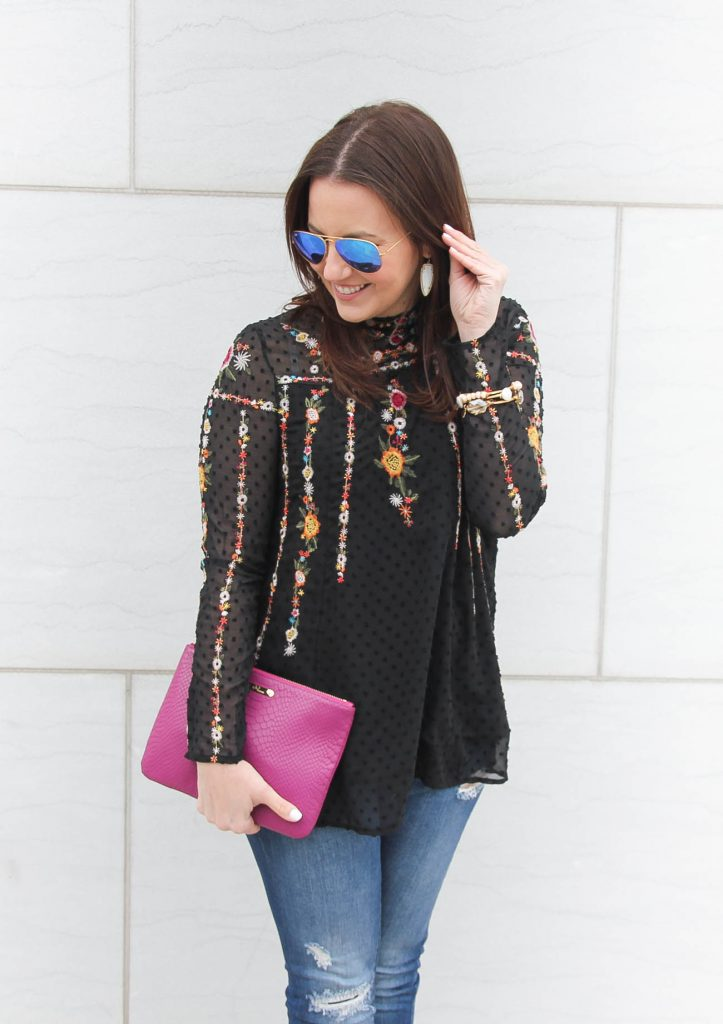 Houston Fashion Blogger styles a floral embroidered top with a dark pink clutch.