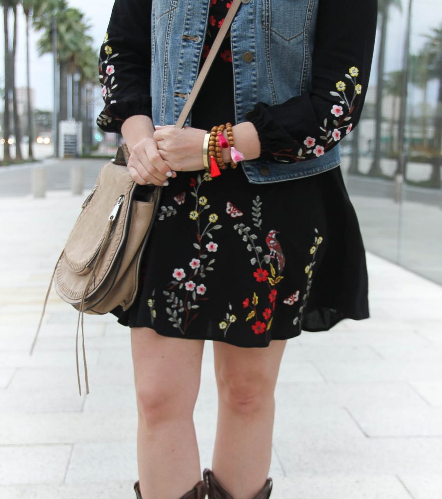 Houston Fashion Blogger styles a rodeo outfit including beaded tassel bracelets, an embroidered dress, and saddle bag.