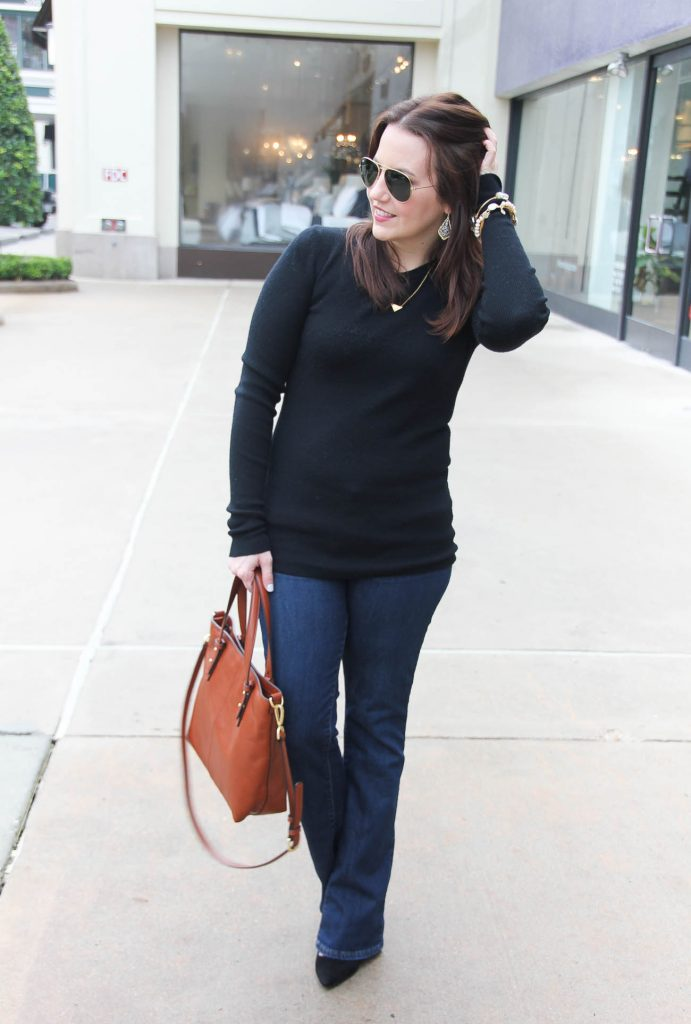 Karen Rock the Houston fashion blogger behind Lady in Violet wears a casual Friday office outfit for winter including a black sweater, flared jeans and lace up heels.