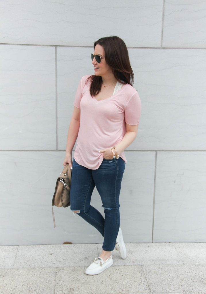Houston fashion blogger styles a comfy travel outfit for a road trip including a pink tee, distressed jeans, and white sperry shoes.