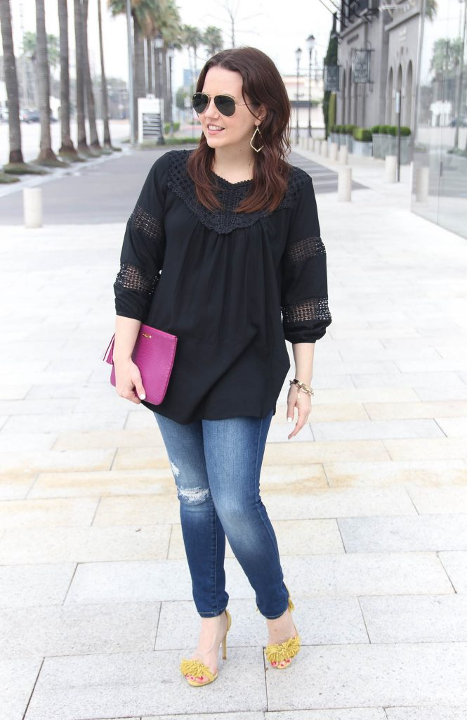 Houston Fashion Blogger styles spring outfit featuring black crochet top with distressed jeans and yellow fringe heels.