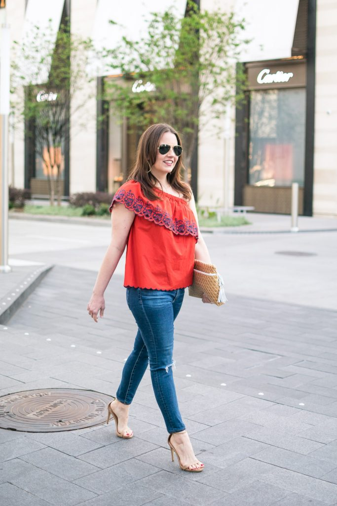 Houston fashion blogger styles a spring outfit idea including a red one shoulder top with distressed jeans and heels.