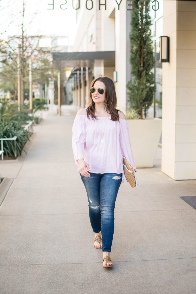 Lady in Violet, a Houston based fashion blogger, wears a pink cold shoulder top with distressed jeans and tory burch sandals for spring outfit inspiration.
