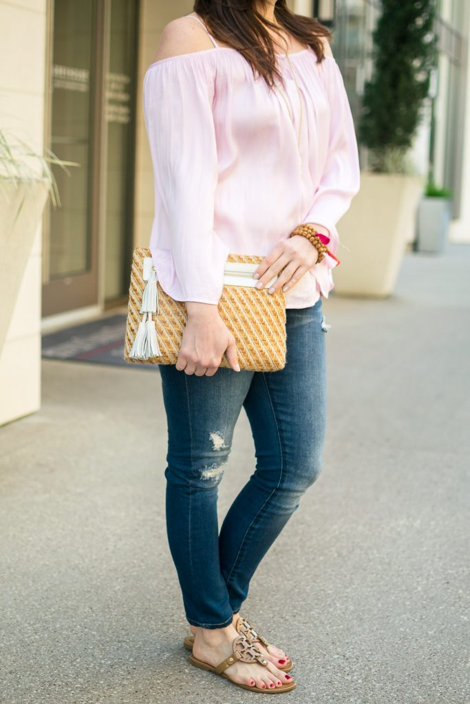 Houston fashion blogger styles a cute casual weekend outfit featuring a pink cold shoulder top with distressed jeans and a straw clutch.