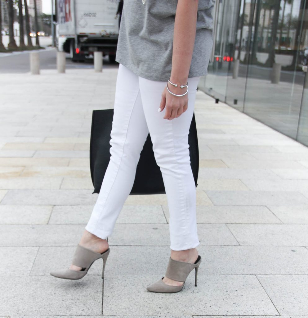 Houston fashion blogger wears gray tee with white jeans and gray mules for spring fashion outfit.