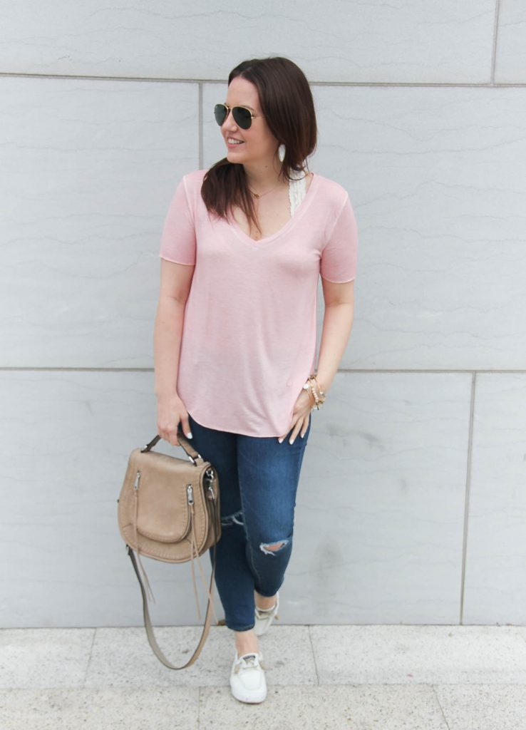Houston fashion blogger, Lady in Violet, styles a comfy road trip outfit featuring a pink tee, skinny jeans, and white sneakers.